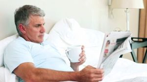 reading newspaper in bed